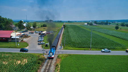 Ronks, Pennsylvania,June 2019 - Aerial Head on View of Thomas the Tank Engine Approaching Thru Trees and Farmlands Pulling Passenger Cars Blowing Smoke on a Beautiful Summer Day Editoriali