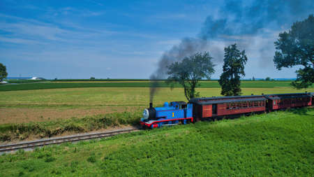 Ronks, Pennsylvania,June 2019 - Aerial View of Thomas the Tank Engine Approaching Thru Trees and Farmlands Pulling Passenger Cars Blowing Smoke on a Beautiful Summer Day Editoriali
