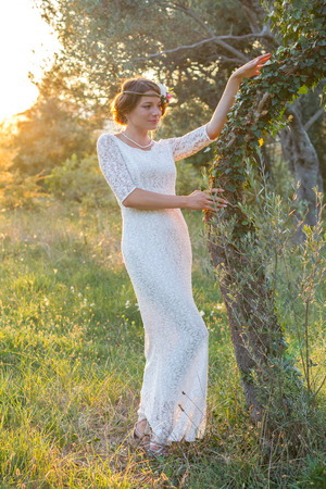marge: girl near a tree at sunset with a wreath in lace dress