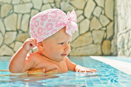 slap: little girl in the swimming pool raised her hand to slap the water