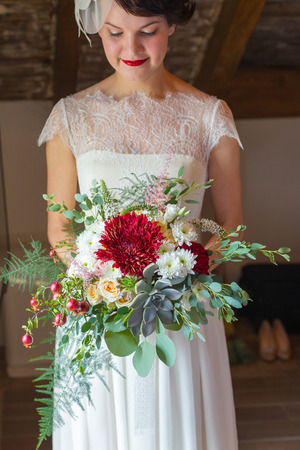 Portrait of a bride who is looking at bridal bouquet