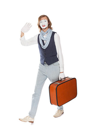 stride: actor mime waves his hand walking with orange suitcase