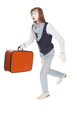 llegar tarde: actor de mimo con una cara de susto se est� ejecutando con una maleta en la mano Foto de archivo