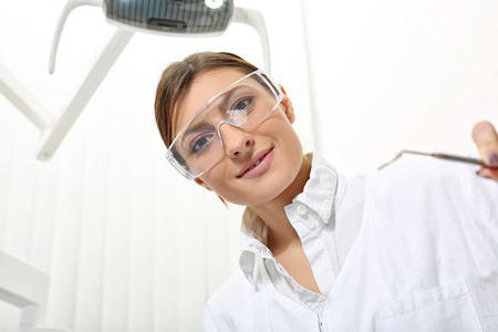 protective glasses: beautiful woman dentist in protective glasses ready to examine the patient