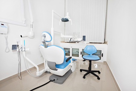Modern dentists chair in a dental office with X-ray and sensory lamp photo