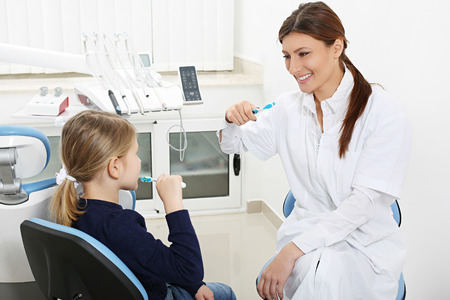 dentist showing girl how correctly to brush your teeth