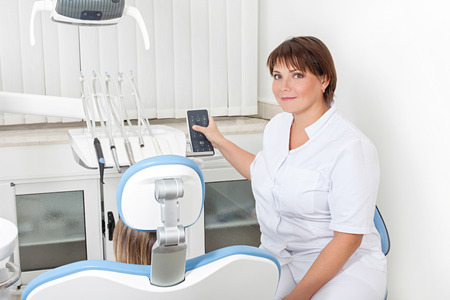 woman dentist in the workplace regulates the chair with the patient Banco de Imagens - 37442726