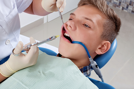 an injection of anesthesia to the patient before dental treatment Stock Photo