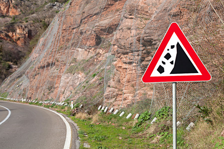 rockfall warning sign on the background of the crumbling hillside covered with protective metal mesh