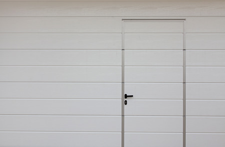 Modern garage door. Large automatic up and over garage door with inclusion of smaller personal door.