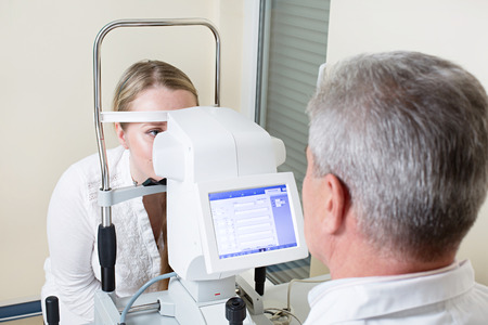 doctor of optometry: Optometry concept -  young woman having her eyes examined by an eye handsome elderly doctor. Topography of the cornea