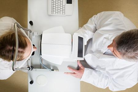 topografia: Concepto de la optometría - mujer joven con los ojos examinados por un ojo médico guapo ancianos. Topografía de la córnea