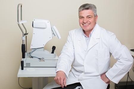 Optometry concept -  portrait of handsome elderly eye doctor 스톡 콘텐츠