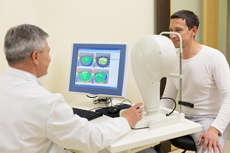 Optometry concept - man having his eyes examined by an eye  elderly doctor. Topography of the cornea.
