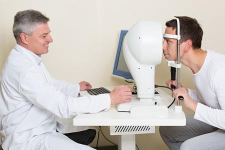 topography: Concepto de Optometr�a - hombre que hace sus ojos examinados por un ojo ancianos m�dico. Topograf�a de la c�rnea.