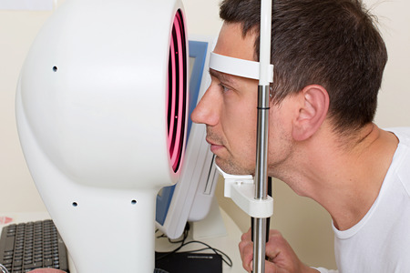doctor of optometry: Optometry concept - man having his eyes examined by an eye  elderly doctor. Topography of the cornea.