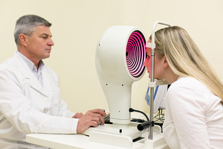 examined: Optometry concept -  young woman having her eyes examined by an eye handsome elderly doctor. Topography of the cornea. Stock Photo