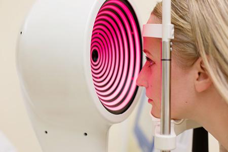 Optometry concept -  young woman having her eyes examined by an eye handsome elderly doctor. Topography of the cornea. Archivio Fotografico