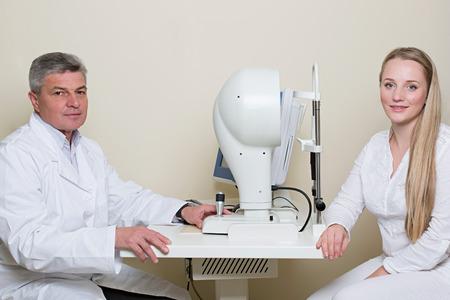 topografia: Concepto de la optometría - mujer joven con los ojos examinados por un ojo médico guapo ancianos. Topografía de la córnea. Foto de archivo