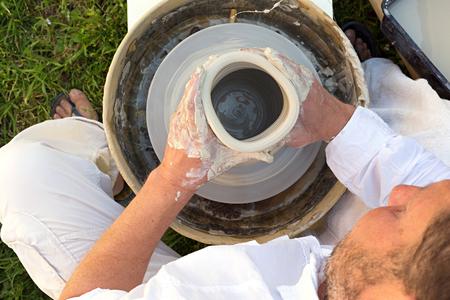 alfarero: alfarero trabajando en una rueda de alfarero con arcilla blanca