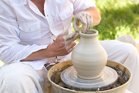 potters wheel: potter working on a potters wheel with white clay
