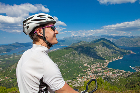 Cyclist on the top of a hill looking away