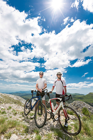 stopped: two cyclists stopped in the mountains to enjoy the view