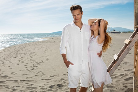 30 years old married couple: Happy loving couple at white clothes enjoy a hot summer day on a beach near the lifeguard tower Stock Photo