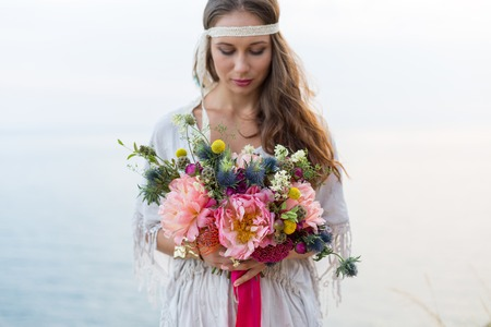 wedding: girl with a wedding bouquet boho style, sea background