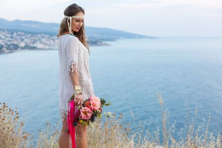 squaw: girl with a wedding bouquet boho style, sea background