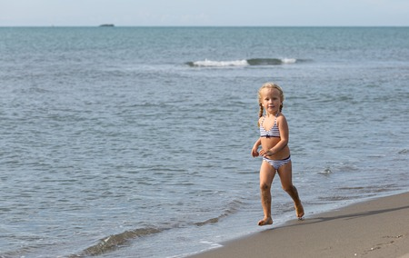 waters  edge: Girl runs along the beach at the waters edge