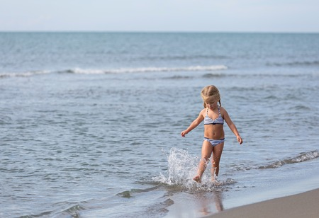 little girl swimsuit: Girl runs along the beach at the waters edge