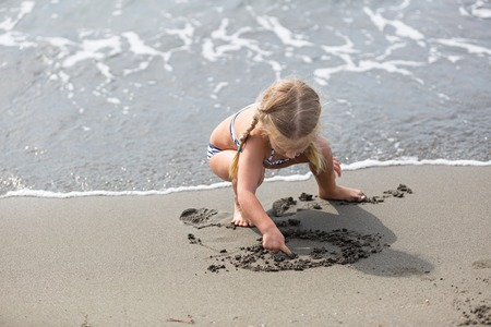 little girl sitting: Little girl sitting on the beach in the sand and draws by finger Stock Photo