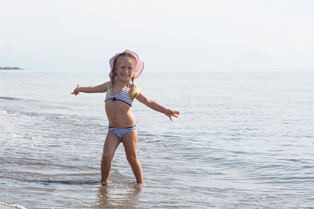 water's edge: little girl sits at the waters edge Stock Photo