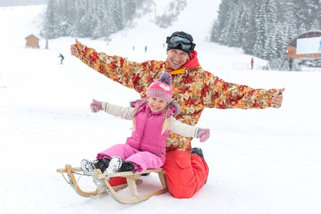 sledging people: Dad and daughter posing sitting on a sled in the winter outdoors