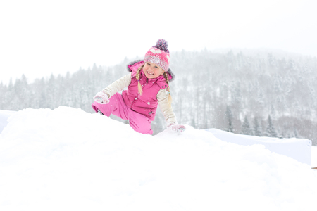 little girl happily playing in the snow outdoors Stock Photo