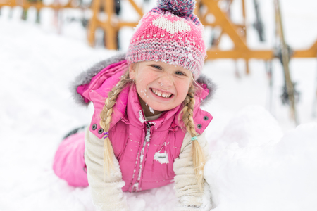 sledging people: little girl happily playing in the snow outdoors Stock Photo