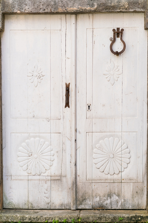 white door: old white closed door view from the street Stock Photo