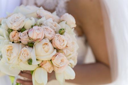 een bruidsboeket van rozen en tulpen die de bruid vasthoudt