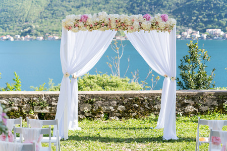 arch for the wedding ceremony, decorated with cloth and flowers, sea in the background Stock Photo