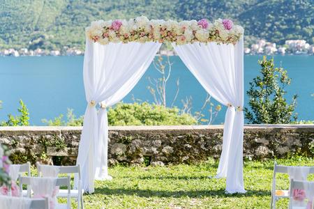 feier: Bogen für die Trauung, mit Tuch und Blumen geschmückt, Meer im Hintergrund