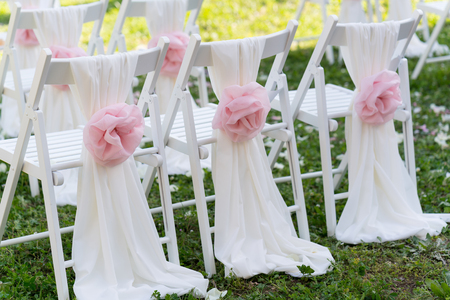 Close-up of white wedding chairs with pink bow in the form of roses