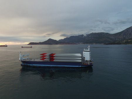 aero generator: Aerial view of a cargo vessel loaded with rotor blades for wind turbines, taken at sunset