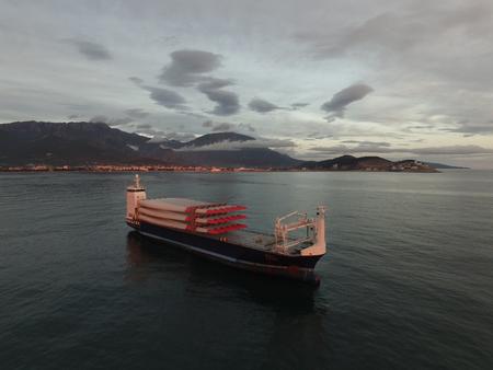 日没で撮影、風力タービンの回転翼搭載貨物船の空撮