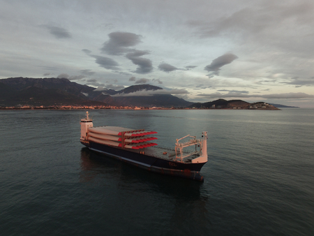 Aerial view of a cargo vessel loaded with rotor blades for wind turbines, taken at sunset