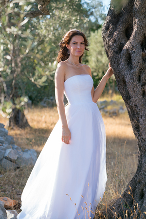 Attractive young woman enjoying her time outside in olive trees with sunset in background.