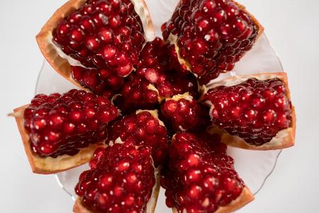 splintered fresh pomegranate on plate close up