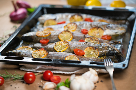 brown trout: delicious trout fish baked with lemon, tomatoes and spices in baking sheet