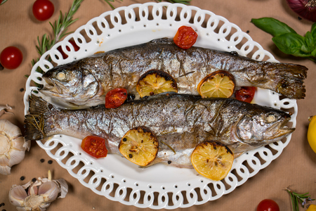 flesh eating animal: delicious trout fish baked with lemon, tomatoes and spices on a white plate Stock Photo