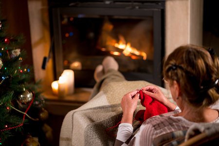 Grandmother knits a sweater sitting in front of a fireplace in the evening